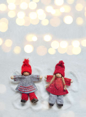 Little Christmas dolls ornaments making angels in the snow as if they were children with lights bokeh. Copy space