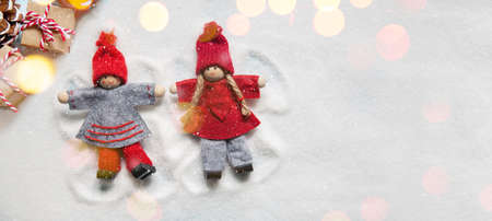 Little Christmas dolls ornaments making angels in the snow as if they were children with lights bokeh and presents. Copy space