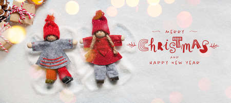 Christmas greeting card with little Christmas dolls ornaments making angels in the snow with lights bokeh. Funny handwriting lettering Banque d'images