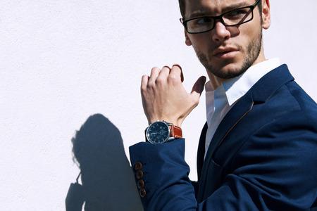 moda: Consider�vel homem usando �culos de moda jovem de encontro ao fundo neutro com lotes do espa�o da c�pia