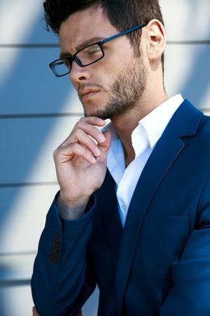 Elegante jonge knappe man draagt een bril en watchers. Portret in de zon.