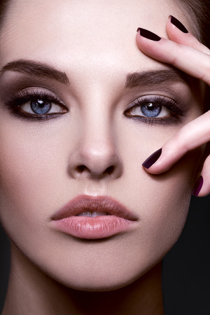 Close-up beauty portrait of beautiful model with bright make-up and manicure