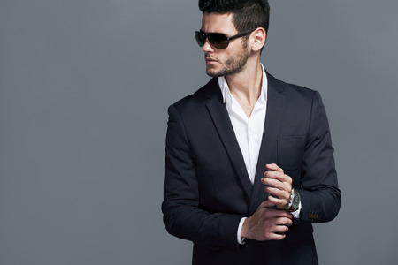 man in suit: Elegant young handsome man wearing glasses and wathers. Stock Photo