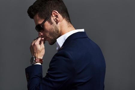 Elegante jonge knappe man draagt ??een bril en wathers. Stockfoto - 50573933