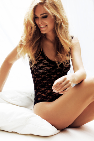 mujer rubia desnuda: Mujer rubia sexy posando en la cama blanca