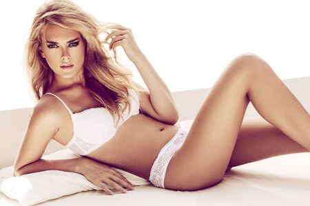 mujer sexy desnuda: Mujer rubia sexy posando en la cama blanca