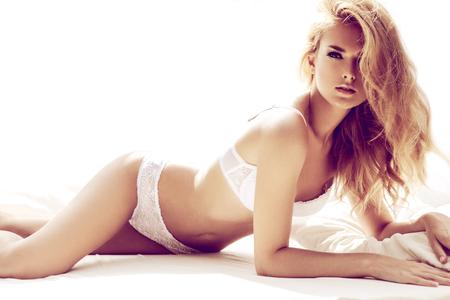 modelo desnuda: Mujer rubia sexy posando en la cama blanca
