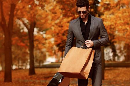 Hermoso hombre de traje con bolsas de la compra. Otoño.