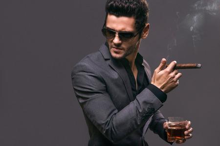 Ernstige zakenman rookt zijn sigaar grijze achtergrond Stockfoto