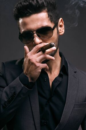 male hand: Serious business man is smoking his cigar gray background Stock Photo