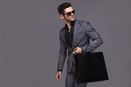 fashion sunglasses: Handsome man in suit with shopping bag