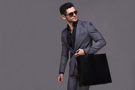 traje formal: Hombre hermoso en juego con el bolso de compras Foto de archivo