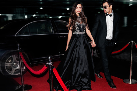 Sexy couple in the car. Hollywood star. Fashionable pair of elegant people at night city street. photo
