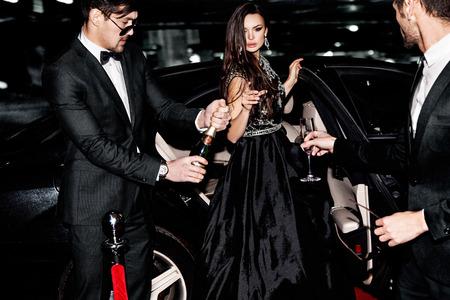 Friends near the car. Hollywood star. Celebrating.