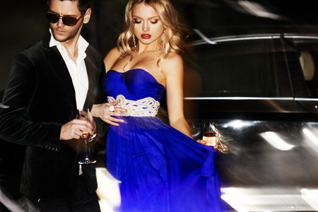 club dress: Sexy couple in the car. Hollywood star. Fashionable pair of elegant people at night city street.