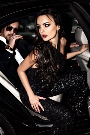 woman red dress: Sexy couple in the car. Hollywood stars. Stock Photo