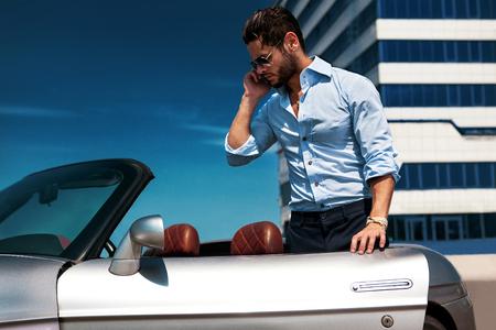 Knappe man in de buurt van de auto. Luxe leven. Stockfoto
