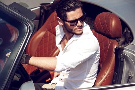 車の近くのハンサムな男性。贅沢な生活。
