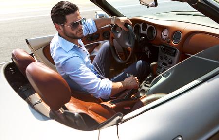 Przystojny mężczyzna w pobliżu samochodu. Luksusowe życie.
