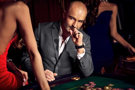 Handsome man playing in casino Standard-Bild