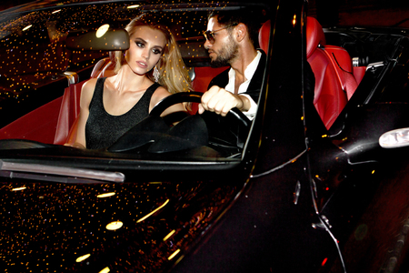 Couple in luxury car. Night life.