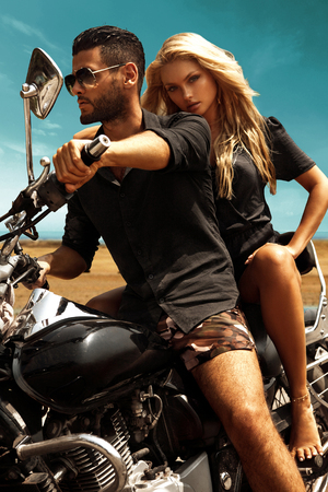 Man riding on a motorcycle with girlfriend on road. Stock Photo