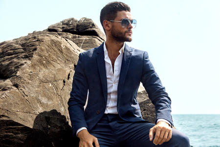Man in elegant suite posing in rock background Imagens