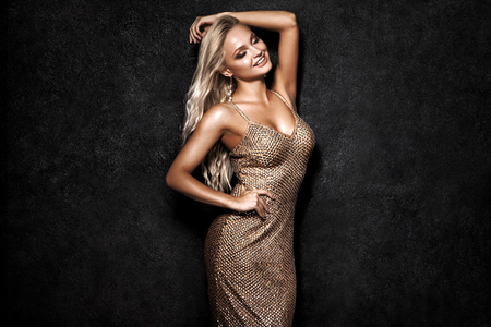 Beautiful sexy blonde woman on black background, party. Banque d'images