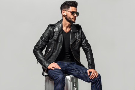 Elegant young handsome man with luggage. Studio fashion portrait.