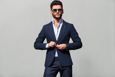 Elegant young handsome man in suite wearing glasses. Studio fashion portrait.