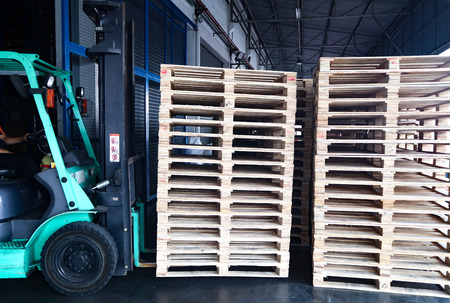 The forklift and wooden pallets in the cargo warehouse for transportation and logistics