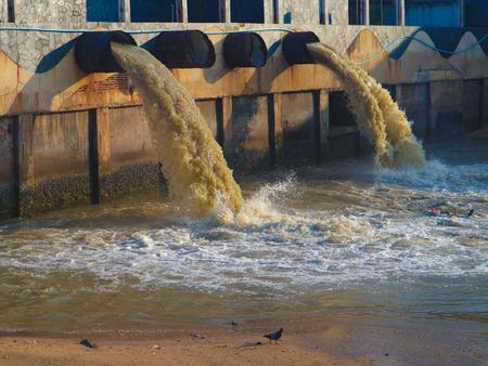 Tubería de descarga de aguas residuales industriales y de fábrica en el canal y el mar Foto de archivo