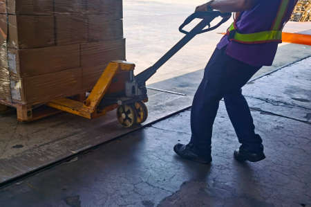 Worker loading and unloading shipment carton boxes and goods on wooden pallet by forklift  from container truck to warehouse cargo storage in logistics and transportation industrial