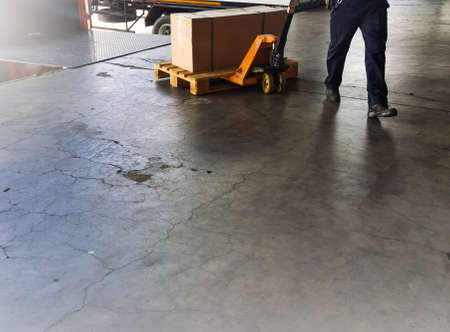 Worker driving forklift loading and unloading shipment carton boxes and goods on wooden pallet from container truck to warehouse cargo storage in logistics and transportation industrial