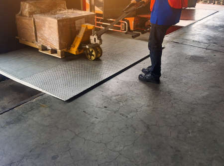 Worker driving forklift loading shipment carton boxes and goods on wooden pallet at loading dock from container truck to warehouse cargo storage in freight logistics and transportation industria Stock Photo