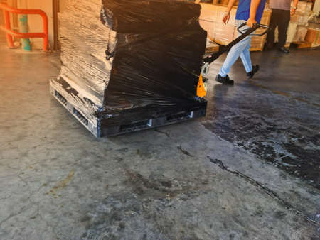 Worker driving forklift loading shipment carton boxes and goods on wooden pallet at loading dock from container truck to warehouse cargo storage in freight logistics and transportation industrial