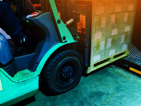 Worker driving forklift loading shipment carton boxes and goods on wooden pallet at loading dock from container truck to warehouse cargo storage in freight logistics and transportation industrial 스톡 콘텐츠 - 154249803