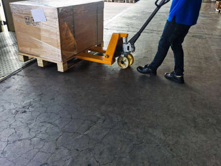 Worker driving forklift loading shipment carton boxes and goods on wooden pallet at loading dock from container truck to warehouse cargo storage in freight logistics and transportation industrial 스톡 콘텐츠 - 154249813