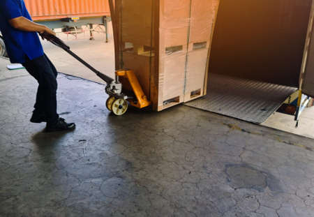 Worker driving forklift loading shipment carton boxes and goods on wooden pallet at loading dock from container truck to warehouse cargo storage in freight logistics and transportation industrial 스톡 콘텐츠 - 154249819