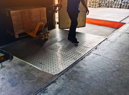 Worker driving forklift loading shipment carton boxes and goods on wooden pallet at loading dock from container truck to warehouse cargo storage in freight logistics and transportation industrial 스톡 콘텐츠 - 154249820
