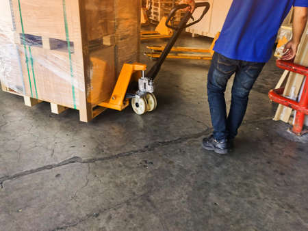 Worker driving forklift loading shipment carton boxes and goods on wooden pallet at loading dock from container truck to warehouse cargo storage in freight logistics and transportation industrial 스톡 콘텐츠 - 154249822
