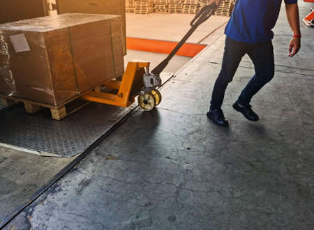 Worker driving forklift loading shipment carton boxes goods on wooden pallet at loading dock from container truck to warehouse cargo storage in freight logistics, transportation industrial, delivery 스톡 콘텐츠 - 154339206