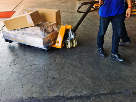 Worker driving forklift loading shipment carton boxes goods on wooden pallet at loading dock from container truck to warehouse cargo storage in freight logistics, transportation industrial, delivery 스톡 콘텐츠 - 154339228