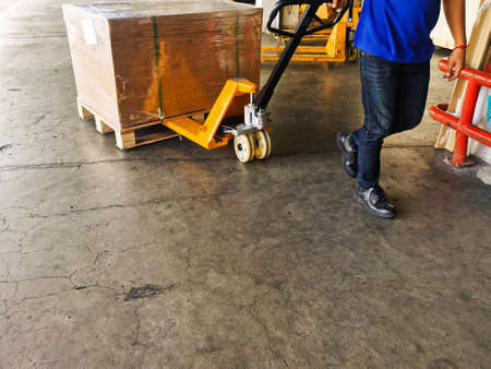 Worker driving forklift loading shipment carton boxes goods on wooden pallet at loading dock from container truck to warehouse cargo storage in freight logistics, transportation industrial, delivery 스톡 콘텐츠 - 154339698