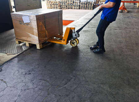 Worker driving forklift loading shipment carton boxes goods on wooden pallet at loading dock from container truck to warehouse cargo storage in freight logistics, transportation industrial, delivery 스톡 콘텐츠 - 154339740