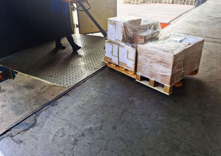 Worker driving forklift loading shipment carton boxes goods on wooden pallet at loading dock from container truck to warehouse cargo storage in freight logistics, transportation industrial, delivery 스톡 콘텐츠 - 154339741
