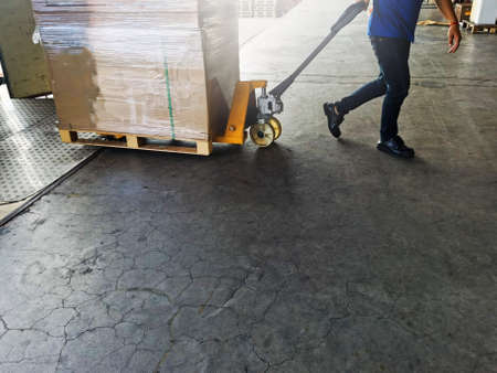 Worker driving forklift loading shipment carton boxes goods on wooden pallet at loading dock from container truck to warehouse cargo storage in freight logistics, transportation industrial, delivery 스톡 콘텐츠 - 154339782
