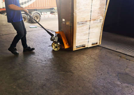 Worker driving forklift loading shipment carton boxes goods on wooden pallet at loading dock from container truck to warehouse cargo storage in freight logistics, transportation industrial, delivery 스톡 콘텐츠 - 154339799