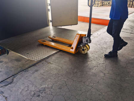 Worker driving forklift loading shipment carton boxes goods on wooden pallet at loading dock from container truck to warehouse cargo storage in freight logistics, transportation industrial, delivery 스톡 콘텐츠 - 154339804
