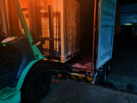 Worker driving forklift loading shipment carton boxes goods on wooden pallet at loading dock from container truck to warehouse cargo storage in freight logistics, transportation industrial, delivery 写真素材